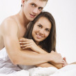 Young couple sitting in bed — Stock Photo