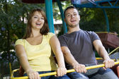 Laughing couple on the carousel — Stock Photo