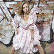 Fashion model in dress against the wall with graffiti — Stock Photo