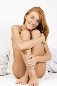 Sexyl naked girl sitting on bed — Stock Photo