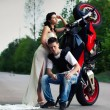 Pretty couple near breakdowned motorbike on the center of the rural road. — Stock Photo #3179067