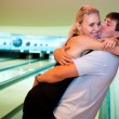 Pretty embracing couple in the bowling club. — Stock Photo