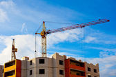 Two cranes and house construction — Stock Photo