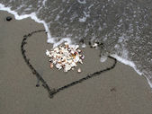 Рainted heart on the beach swept away — Stock Photo