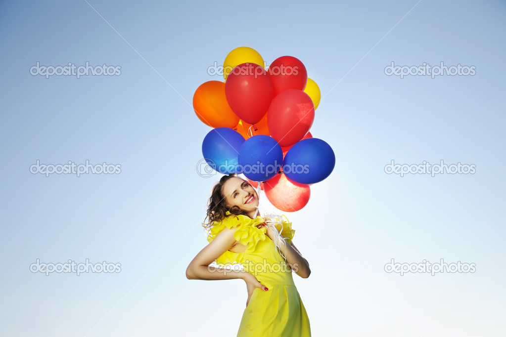 Woman holding balloons against sun and sky  Stock Photo #3503415