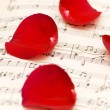 Red rose petals on musical notes — Stock Photo