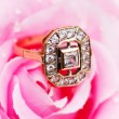 Golden ring and rose at the background — Stock Photo