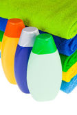 Bottles of shampoo and colour terry towels — Stock Photo
