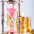 Hourglass and coins — Stock Photo #3896754