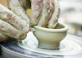 Potters hands creating a clay masterpiece at the turning wheel. — Stock Photo