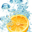 Bubbles forming in blue water after orange is dropped into it. — Stock Photo