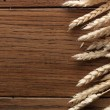 Wheat spikes on wooden board — Stock Photo