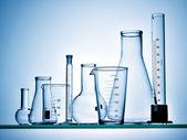 Laboratory glassware on blue background — Stock Photo