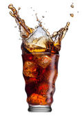 Ice cube droped in cola glass and cola splashing — Stock Photo