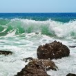 Rocks in the waves and sea foam. — Stock Photo