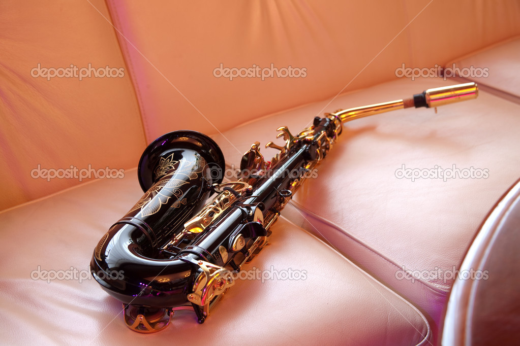 Saxophone lying on the sofa — Stock Photo #3388978