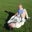 Son on father lie on grass — Stock Photo #3537625