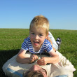 Son lie on ather on green grass — Stock Photo