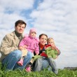 Family of four sit. clouds. grass — Stock Photo #3537658