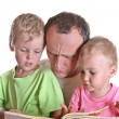 Grandfather read book with children — Stock Photo