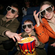 Family in stereo cinema. focus on popcorn - Stock Photo