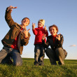 Family with fingers on grass — Stock Photo