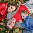 Family on autumn leaves — Stock Photo