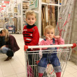 Children in shopingcart and couple — Stock Photo #3538195