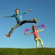 Couples jump on grass — Stock Photo
