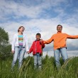 Happy family stand in grass — Stock Photo