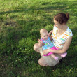 Stock Photo: Mother sitting with baby on meadow