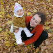 Mother with baby on autumn field from up — Stock Photo #3538430