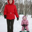 Mother with baby on sled — Stock Photo