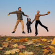 Fly happy family with autumn leaves. color sunset sky — Stock Photo #3538827
