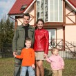 Family of four and house — Stock Photo