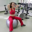 Girl in health club on rubber ball - Stock Photo