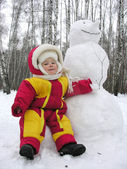 Baby and snowman — Stock Photo