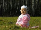 Baby sit on grass in jacket and hat — Stock Photo
