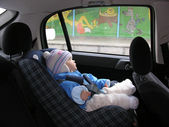 Baby in car with dreams in window — Stock Photo
