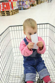 Baby in shopingcart watch check — Stock Photo