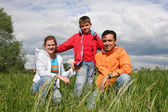 Happy family sit in grass — Stock Photo