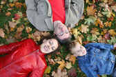 Family lies on maple leaves — Stock Photo