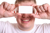 Man with card for text on eyes — Stock Photo