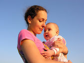 Mother with baby under sky — Stock Photo