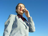 Businesswoman with phone on blue sky from down view — Stock Photo