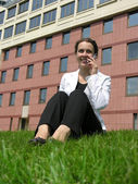 BUSINESSWOMAN AND PHONE IN GRASS — Stock Photo