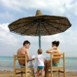 Family under umbrella on beach — Stock Photo