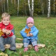 Children sit in autumn park — Stock Photo