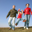 Stock Photo: Running family with child on spring meadow