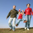 Running family with child on spring meadow — Stock Photo #3540791
